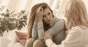 Middle-aged woman psychologyst therapy with client at the office sitting girl looking at therapist upset holding head